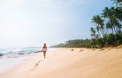 Woman in white swimsuit walks on lonely sand tropical beach Stock Image