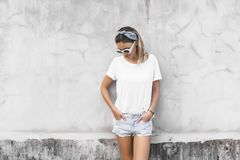 Woman in white t-shirt on grey background. Hipster girl wearing blank white t-shirt and denim shorts posing against gray street wall, blank mockup for tshirt royalty free stock images