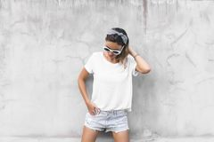 Woman in white t-shirt on grey background. Hipster girl wearing blank white t-shirt and denim shorts posing against gray street wall, blank mockup for tshirt stock images