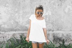 Woman in white t-shirt on grey background. Hipster girl wearing blank white t-shirt and denim shorts posing against gray street wall, blank mockup for tshirt stock photography