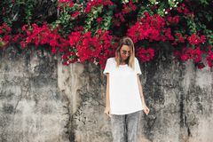 Woman in white t-shirt on grey background with spring flowers. Hipster girl wearing blank white t-shirt posing against gray street wall with spring flowers royalty free stock photos