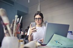 Woman in White T-shirt Holding Smartphone in Front of Laptop Stock Images