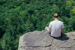 Woman in White T Shirt Sitting on Cliff Above Trees at Daytime Stock Images