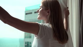 Woman in white t-shirt unveiling curtains and looking out of window. Enjoying sea view outside 100 fps stock video