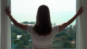 Woman in white t-shirt unveiling curtains and looking out of window. Enjoying the sea view outside stock video footage
