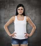 A woman in a white tank top and denims. Hands are in the pockets. Black chalk board on background. A brunette woman in a white tank top and denims. Hands are in Royalty Free Stock Images