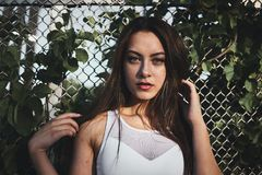 Woman in White Tank Top Standing Near Gray Metal Wire Fence Stock Images