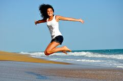 Woman in White Tanktop Jump over Beach Sand Royalty Free Stock Photos