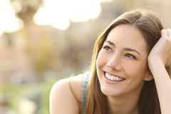 Woman with white teeth thinking and looking sideways Royalty Free Stock Photography