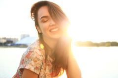 Woman with white teeth thinking and looking sideways in a park in summer Stock Photos