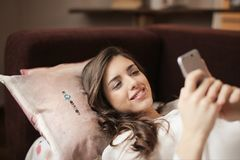 Woman in White Top Holding Smartphone Lying on Couch Royalty Free Stock Image
