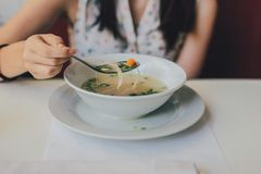 Woman in White Tops Eating Soup on Ceramic Bowl Royalty Free Stock Photo