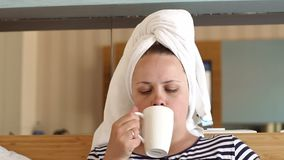 Woman in white towel drinking coffee or tea in bed in hotel room or home bedroom. Beautiful young girl holding cup of coffee and sitting in bed stock video footage