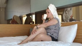 Woman in white towel drinking coffee or tea in bed in hotel room or home bedroom. A young woman in shorts, a striped t-shirt and a towel on her head sits on a stock footage