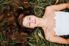 Woman in White Tube Dress Lying on Green Grass in Closed Eyes Royalty Free Stock Images