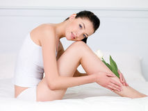 Woman with white tulip on a perfect legs Royalty Free Stock Photo