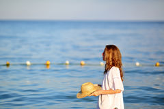 Woman in white tunic and straw hat in hands on the beach Stock Photos