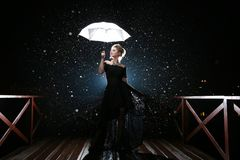 Woman with white umbrella in flash lights and rain drops royalty free stock photography