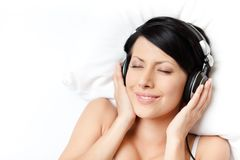 Woman in white underwear listens to music Royalty Free Stock Photos