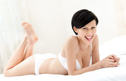 Woman in white underwear is lying in bed Stock Photo