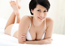 Woman in white underwear is lying in the bed Royalty Free Stock Photography