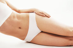 Woman in white underwear lying on her side on white background while her hand on a tip. Isolated on white. Stock Photography
