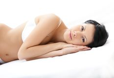 Woman in white underwear is lying in the wide bed Royalty Free Stock Photo