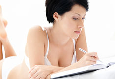 Woman in white underwear makes some notes Royalty Free Stock Image