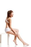 Woman in white underwear touching her leg Stock Photo