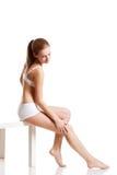 Woman in white underwear touching her leg Stock Photo