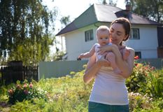 Woman in white vest holding baby on arms outdoors stock photo