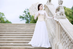 Woman in white Victorian dress with umbrella Stock Image