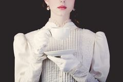 Woman in white victorian era clothes with cup of tea. Young redhead woman in white victorian era clothes with cup of tea on black background royalty free stock photos