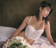 Woman in White Vintage Lingerie on Bed Stock Images