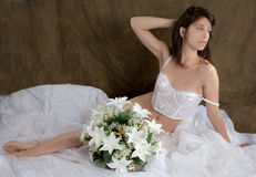 Woman in White Vintage Lingerie on Bed Royalty Free Stock Photography
