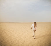 Woman in white walking on the desert Royalty Free Stock Images