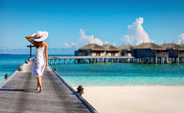 Woman in white walking over a wooden jetty. In the Maldives Stock Photo