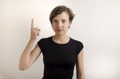 Woman on a white wall raises her forefinger Royalty Free Stock Image