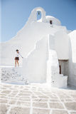Woman in a white-washed Greek villa. Woman in a white-washed villa complex in Greece with the typical Mediterranean architecture stock photos