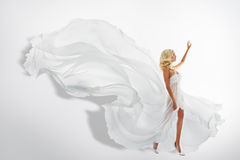 Woman White Waving Dress, Showing Hand Up, Flying Silk Fabric. Woman White Waving Dress, Showing Hand Up, Flying Fabric, Silk Cloth Flowing on wind, over white Stock Photography
