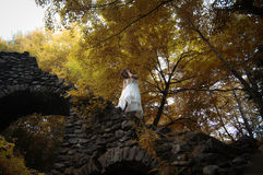 Woman in white. Woman wearing a white dress in the forest. She is looking back while making her way down an old stone staircase Stock Image