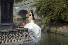 A woman with white wedding dress carry bridal bouquet sit on a cloister in shui bo park of Shanghai Royalty Free Stock Images