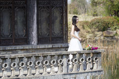 A woman with white wedding dress carry bridal bouquet stand in a cloister in shui bo park of Shanghai Royalty Free Stock Images