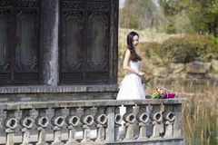 A woman with white wedding dress carry bridal bouquet stand in a cloister in shui bo park of Shanghai Stock Image