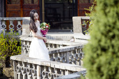 A woman with white wedding dress carry bridal bouquet stand in a cloister in shui bo park of Shanghai Royalty Free Stock Photography