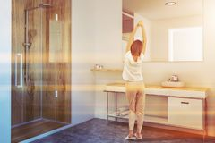 Woman in a white and wooden bathroom. Woman in a luxury bathroom interior with a wooden shower stall, a sink vanity unit and a large mirror. Side view 3d royalty free stock photos
