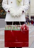 Woman in white wool coat and gloves holding shopping bag with Christmas gifts presents wrapped in festive wrapping paper and bows