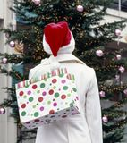Woman in white wool coat and santa hat holding shopping bag with Christmas tree in background. Holiday giving Christmas shopping