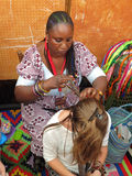 The woman who is braiding. The suq in Genoa Italy Royalty Free Stock Photos