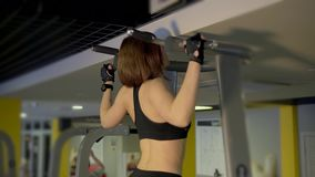 Woman who come to fitness pulls up on the simulator to strengthen the muscles. stock footage